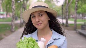 Πορτρέτο ενός όμορφου κοριτσιού που φέρνει μια συσκευασία των φρέσκων προϊόντων με τον ηλιόλουστο καιρό που έχει μια καλή διάθεση απόθεμα βίντεο