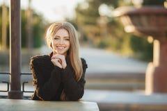 Πορτρέτο ενός όμορφου κοριτσιού σε έναν πίνακα στον καφέ οδών στοκ εικόνες
