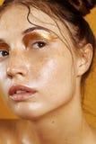 Πορτρέτο ενός όμορφου κοριτσιού σε ένα κίτρινο υπόβαθρο με την επίδραση του υγρού δέρματος Στοκ Φωτογραφία