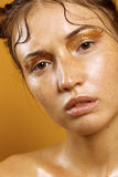 Πορτρέτο ενός όμορφου κοριτσιού σε ένα κίτρινο υπόβαθρο με την επίδραση του υγρού δέρματος Στοκ φωτογραφίες με δικαίωμα ελεύθερης χρήσης