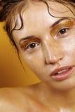 Πορτρέτο ενός όμορφου κοριτσιού σε ένα κίτρινο υπόβαθρο με την επίδραση του υγρού δέρματος Στοκ Φωτογραφίες
