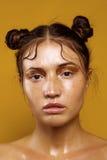 Πορτρέτο ενός όμορφου κοριτσιού σε ένα κίτρινο υπόβαθρο με την επίδραση του υγρού δέρματος Στοκ εικόνες με δικαίωμα ελεύθερης χρήσης