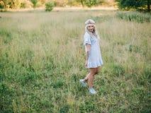 Πορτρέτο ενός όμορφου κοριτσιού σε ένα μπλε φόρεμα με έναν πονοκέφαλο σε έναν τομέα στο ηλιοβασίλεμα το καλοκαίρι Περιστασιακά θε στοκ εικόνες
