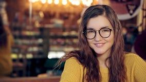 Πορτρέτο ενός όμορφου κοριτσιού σε μια άνετη καφετερία με τα γυαλιά φιλμ μικρού μήκους