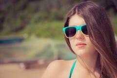 Πορτρέτο ενός όμορφου κοριτσιού στα ζωηρόχρωμα γυαλιά ηλίου στην παραλία Στοκ Φωτογραφία