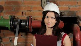 Πορτρέτο ενός όμορφου μηχανικού γυναικών brunette καυκάσιου Ένας επιθεωρητής γυναικών σε ένα άσπρο σκληρό καπέλο χαμογελά ενάντια απόθεμα βίντεο