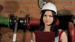Πορτρέτο ενός όμορφου μηχανικού γυναικών brunette καυκάσιου Ένας επιθεωρητής γυναικών σε ένα άσπρο σκληρό καπέλο στο κλίμα φιλμ μικρού μήκους