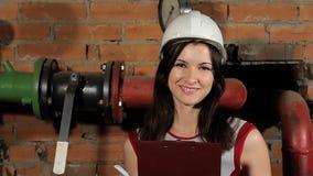 Πορτρέτο ενός όμορφου μηχανικού γυναικών brunette καυκάσιου Ένας επιθεωρητής γυναικών σε ένα άσπρο σκληρό καπέλο που γελά ενάντια απόθεμα βίντεο