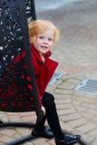Πορτρέτο ενός όμορφου μικρού κοριτσιού με την κόκκινη τρίχα σε ένα κόκκινο παλτό Στοκ Εικόνες