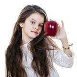Πορτρέτο ενός όμορφου μικρού κοριτσιού που κρατά ένα κόκκινο μήλο Στοκ Εικόνα