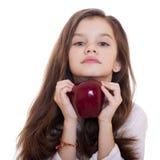 Πορτρέτο ενός όμορφου μικρού κοριτσιού που κρατά ένα κόκκινο μήλο Στοκ Εικόνες