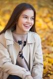 Πορτρέτο ενός όμορφου μικρού κοριτσιού brunette, πάρκο φθινοπώρου υπαίθρια στοκ εικόνα