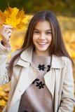 Πορτρέτο ενός όμορφου μικρού κοριτσιού brunette, πάρκο φθινοπώρου υπαίθρια στοκ φωτογραφίες