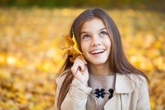 Πορτρέτο ενός όμορφου μικρού κοριτσιού brunette, πάρκο φθινοπώρου υπαίθρια στοκ εικόνα με δικαίωμα ελεύθερης χρήσης