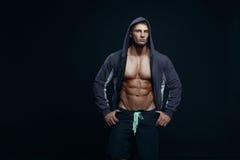 Πορτρέτο ενός όμορφου μυϊκού bodybuilder στο hoodie που θέτει ove Στοκ Εικόνες
