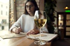 Πορτρέτο ενός όμορφου νέου γυναικών κρασιού και της κατοχής ποτών άσπρου του υπολοίπου στον καφέ κοντά στο παράθυρο Στοκ Εικόνες