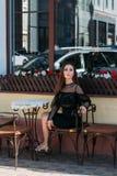 Πορτρέτο ενός όμορφου, νέου, ελκυστικού κοριτσιού που κάθεται στην οδό σε έναν καφέ περιμένοντας το πρόγευμα, καλοκαίρι, ημερομην στοκ εικόνα