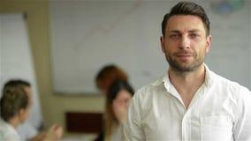 Πορτρέτο ενός όμορφου νέου επιχειρησιακού ατόμου που στέκεται σε ένα γραφείο Έξυπνος καυκάσιος νέος αρσενικός σχεδιαστής με τους  φιλμ μικρού μήκους