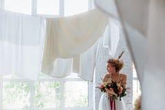 Πορτρέτο ενός όμορφου νέου κοριτσιού με μια ανθοδέσμη που δημιουργεί ένα γαμήλιο φόρεμα στοκ εικόνα με δικαίωμα ελεύθερης χρήσης