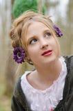 Πορτρέτο ενός όμορφου νέου κοριτσιού με τα διακοσμητικά λουλούδια στο χ Στοκ Φωτογραφίες