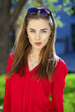 Πορτρέτο ενός όμορφου νέου κοριτσιού στο κόκκινο πουκάμισο στο backgroun Στοκ Εικόνα