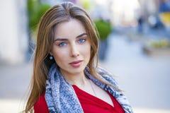 Πορτρέτο ενός όμορφου νέου κοριτσιού στο κόκκινο πουκάμισο στο backgroun Στοκ Φωτογραφία