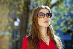 Πορτρέτο ενός όμορφου νέου κοριτσιού στο κόκκινο πουκάμισο στο backgroun Στοκ Εικόνες