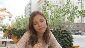 Πορτρέτο ενός όμορφου νέου κοριτσιού, τρώει το παγωτό σε έναν καφέ οδών φιλμ μικρού μήκους
