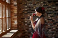 Πορτρέτο ενός όμορφου νέου χορευτή γυναικών σε ένα κόκκινο φόρεμα κοντά στο παράθυρο στοκ εικόνες
