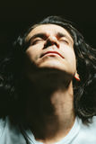 Πορτρέτο ενός όμορφου νεαρού άνδρα με τα μακρυμάλλη βλέμματα επάνω Στοκ φωτογραφίες με δικαίωμα ελεύθερης χρήσης