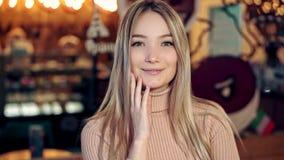 Πορτρέτο ενός όμορφου ξανθού κοριτσιού σε μια άνετη καφετερία φιλμ μικρού μήκους