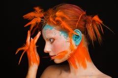Πορτρέτο ενός όμορφου προτύπου με τη δημιουργική σύνθεση και hairstyle τη χρησιμοποίηση των πορτοκαλιών φτερών στοκ εικόνα