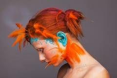 Πορτρέτο ενός όμορφου προτύπου με τη δημιουργική σύνθεση και hairstyle τη χρησιμοποίηση των πορτοκαλιών φτερών στοκ εικόνα με δικαίωμα ελεύθερης χρήσης