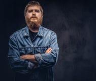 Πορτρέτο ενός όμορφου τύπου hipster που ντύνεται στην τοποθέτηση σακακιών τζιν με τα διασχισμένα όπλα σε ένα σκοτεινό υπόβαθρο στοκ φωτογραφία