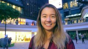 Πορτρέτο ενός όμορφου χαμογελώντας ανατολικού ασιατικού κοριτσιού Στο υπόβαθρο είναι θολωμένα φω'τα μιας μεγάλης υπεραγοράς απόθεμα βίντεο