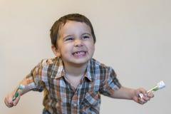 πορτρέτο ενός όμορφου χαριτωμένου καυκάσιου ξανθού αγοριού με μια οδοντόβουρτσα Δόντια βουρτσίσματος μικρών παιδιών και χαμόγελο  στοκ εικόνες