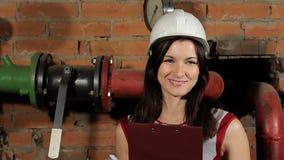 Πορτρέτο ενός όμορφου brunette γέλιου μηχανικών γυναικών καυκάσιου Μια γυναίκα εργαζόμενος σε ένα άσπρο σκληρό καπέλο χαμογελά εν απόθεμα βίντεο
