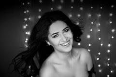 Πορτρέτο ενός όμορφου brunette χαμόγελου με μακρυμάλλη Φωτογραφία στούντιο, bokeh λάμπες φωτός μαύρο λευκό Στοκ φωτογραφίες με δικαίωμα ελεύθερης χρήσης