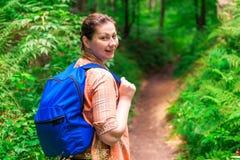 Πορτρέτο ενός brunette με ένα σακίδιο πλάτης σε ένα πράσινο δάσος Στοκ Εικόνα
