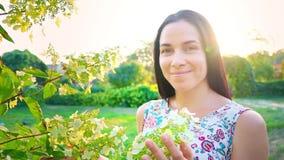 Πορτρέτο ενός brunette χαμόγελου με τα πτυχωμένα μάγουλα ενάντια σε ένα πράσινο πάρκο Όμορφες νέες στάσεις γυναικών στο πάρκο και φιλμ μικρού μήκους