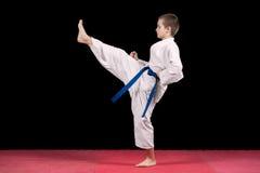 Πορτρέτο ενός karate παιδιού στο κιμονό έτοιμο να παλεψει απομονωμένος στο μαύρο υπόβαθρο Στοκ εικόνα με δικαίωμα ελεύθερης χρήσης