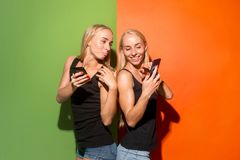 Πορτρέτο ευτυχή χαμογελώντας περιστασιακά κορίτσια με τα κινητά τηλέφωνα πέρα από το υπόβαθρο στούντιο στοκ εικόνα με δικαίωμα ελεύθερης χρήσης