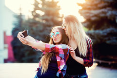 Πορτρέτο ευτυχών δύο χαμογελώντας κοριτσιών που κάνουν selfie τη φωτογραφία στο smartphone ανασκόπηση αστική Το ηλιοβασίλεμα βραδ Στοκ φωτογραφίες με δικαίωμα ελεύθερης χρήσης