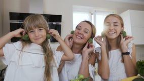 Πορτρέτο Η αστεία, νέα και εύθυμη οικογένεια, παίζει με το μπρόκολο στην κουζίνα μαγειρεύοντας Κινηματογράφηση σε πρώτο πλάνο _ φιλμ μικρού μήκους
