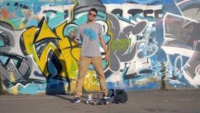 Πορτρέτο καλλιτεχνών γκράφιτι Ο καλλιτέχνης γκράφιτι είναι στάση, τινάζοντας ένα χρώμα ψεκασμού, σακίδιο πλάτης στο έδαφος φιλμ μικρού μήκους