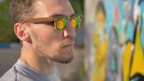 Πορτρέτο καλλιτεχνών γκράφιτι Ο καλλιτέχνης γκράφιτι χρωματίζει, ο τοίχος απεικονίζει στα γυαλιά ηλίου του απόθεμα βίντεο