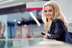 Πορτρέτο καλού νέου ενός ξανθού με το μάτι makeup κινητή τηλεφωνική χαμογελώντας γυναίκα στοκ εικόνα με δικαίωμα ελεύθερης χρήσης
