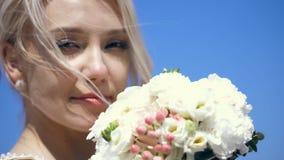 Πορτρέτο, κινηματογράφηση σε πρώτο πλάνο, όμορφη ξανθή νύφη που απολαμβάνει τη μυρωδιά της γαμήλιας ανθοδέσμης άσπρων λουλουδιών  φιλμ μικρού μήκους