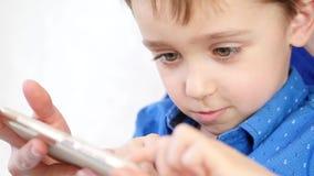Πορτρέτο κινηματογραφήσεων σε πρώτο πλάνο ενός ευτυχούς χαμογελώντας αγοριού Παιχνίδι Mom και μωρών με ένα smartphone Το παιδί αγ απόθεμα βίντεο