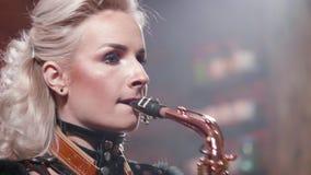 Πορτρέτο κινηματογραφήσεων σε πρώτο πλάνο ενός θηλυκού μουσικού που παίζει εναρέτως σε ένα saxophone απόθεμα βίντεο